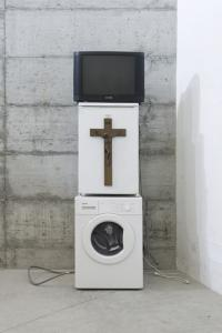 Danh Vo, Oma Totem, 2009<br /> objects from the artist's grandmother Nguyen Thi Ty, received from The Immigrant Relief Program and The Catholic Church on arriving in Denmark:<br /> - 1 Phillips 26 inch TV<br /> - 1 Gorenje washing machine<br /> - 1 Bomann refrigerator<br /> - 1 wooden crucifix<br /> - 1 Nguyen Thi Ty's personalized entrance card for a casino<br /> Courtesy: Galerie Isabella Bortolozzi – Danh Vo<br /> Galleria Zero, Milan; Photographer:  Cosimo Pichierri