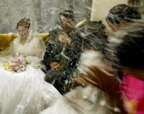 Zohra Bensemra: Iraqi newlyweds Naheb Saidi (L), 25, and Baha Turkeg, 26, are showered in foam during their wedding party in Baghdad July 1, 2004. As the world watched Saddam Hussein's first court appearance, the couple took their vows to lead a new life together. © REUTERS/Zohra Bensemra